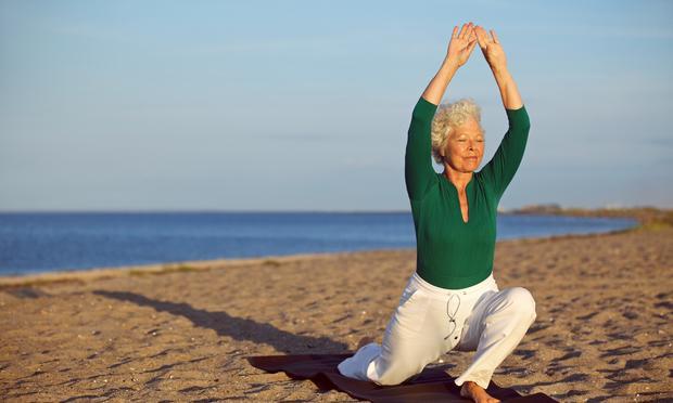 Senior woman practicing yoga poses on the sandy beach.