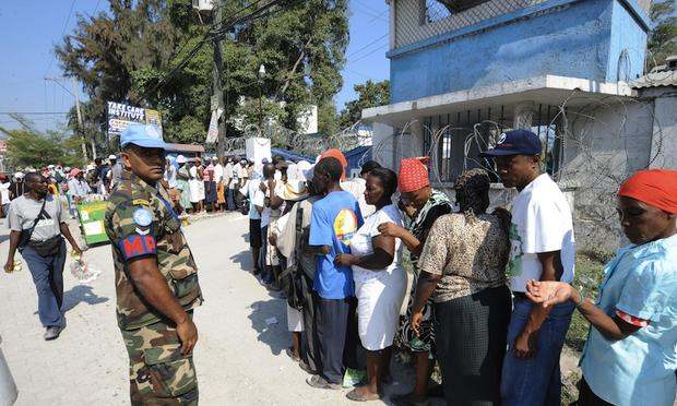 UN police patrol as people wait in line during the distribution of humanitarian aid in Port au Prince on March 11, 2010. President Barack Obama said Wednesday that Haiti's plight was still 'dire' afte