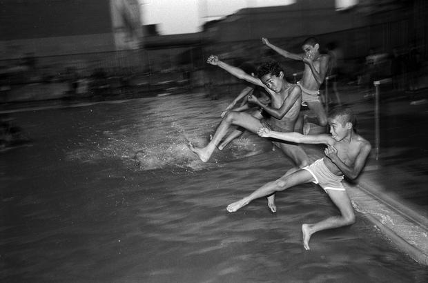 Teenage boys jump into a public swimming pool at night. They climbed over the fence. 1984