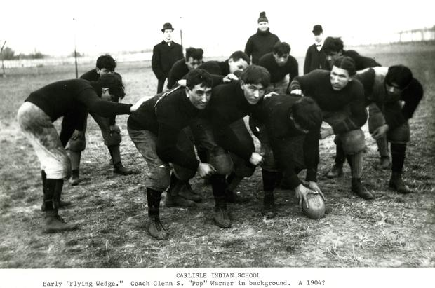 Early 'flying wedge' formation. Possibly 1904. Carlisle Indian School team, with Pop Warner in back.