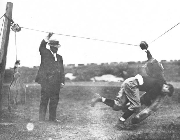 Jim Thorpe attacking an improvised tackling dummy made of weights and pulley on wire, with Coach Warner looking on, c. 1912.