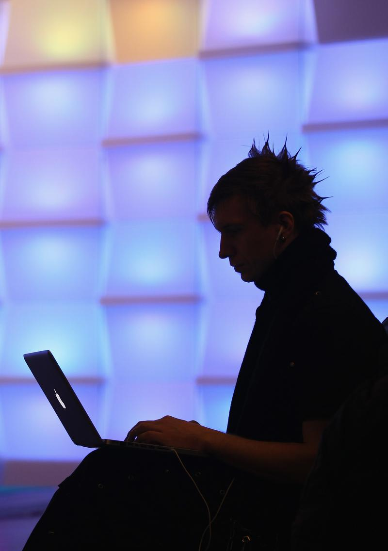 A participant sits with a laptop computer as he attends the annual Chaos Communication Congress of the Chaos Computer Club at the Berlin Congress Center on December 28, 2010.
