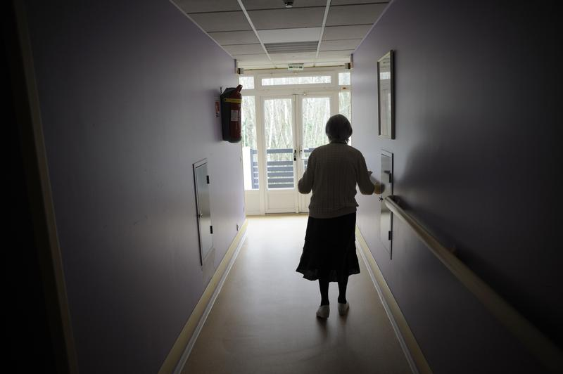 A woman, suffering from Alzheimer's desease, walks in a corridor on March 18, 2011 in a retirement house.