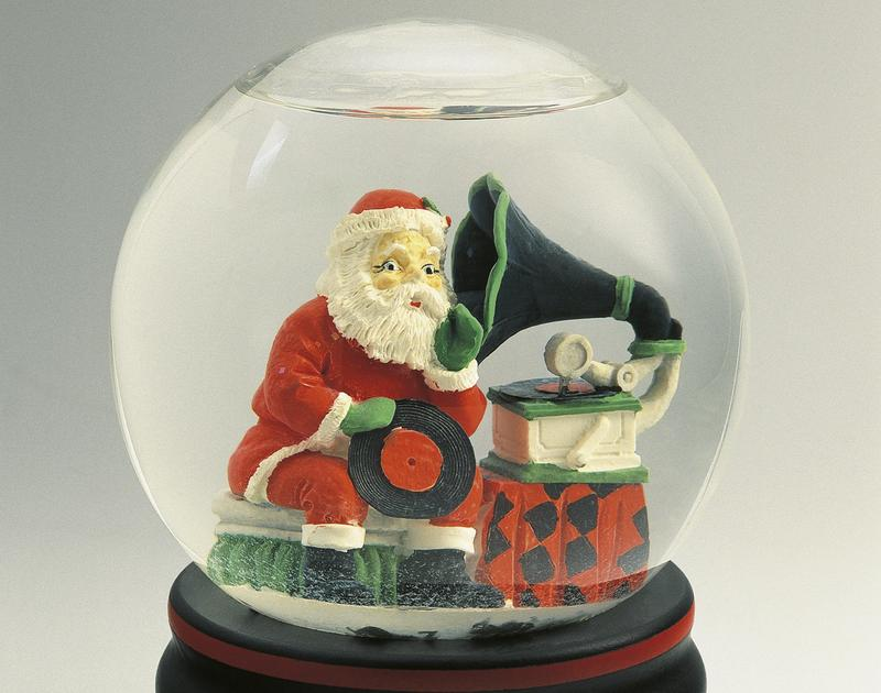 Close-up of a figurine of a Santa Claus listening to a gramophone in a snow globe