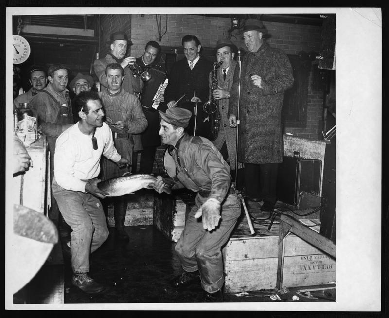 [Louis De Marco and Michael Tolento doing the twist with a fish as Joe Murphy's Filet Harmonicats entertain at Fulton Fish Market] 1962