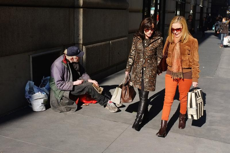 Women walk by a panhandler on Madison Avenue, one of Manhattan's premier streets, on Nov. 1, 2011. Income inequality is greatest in New York State than any where else in the U.S.