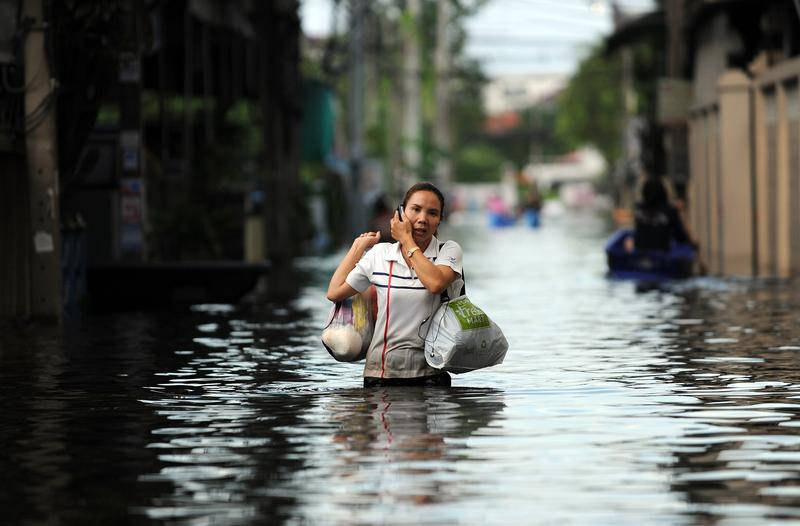 A Thai woman talks on her cell phone while wading through the flood waters in Bangkok on November 7, 2011. The Thai capital is slowly sinking, and floods could get worse from climate change.