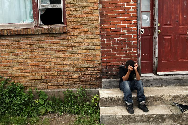 A child sits on a stoop in a working class section of Utica on May 14, 2012 in Utica, New York. The city's individual poverty rate is twice the national average with an unemployment rate of 9.8%.