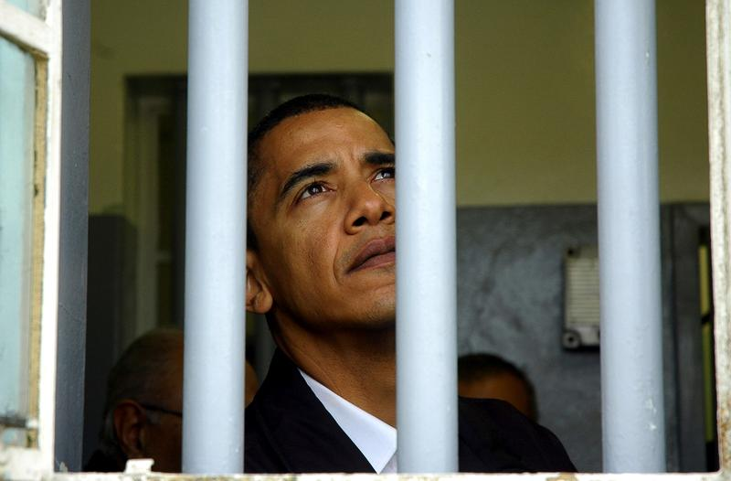 Barack Obama, then a U.S. senator for Illinois, looks out of the window of Nelson Mandela's jail cell on August 20, 2006, on Robben Island, about six kilometres from the city, in Table Bay.