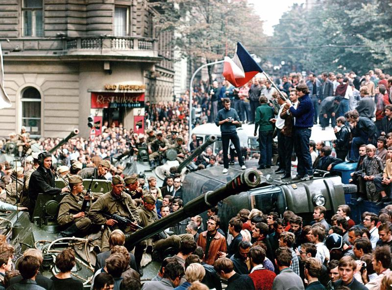 Czech youngsters holding a flag stand atop an overturned truck as other Prague residents surround Soviet tanks on Aug. 21 1968 during the Soviet-led invasion by the Warsaw Pact armies.