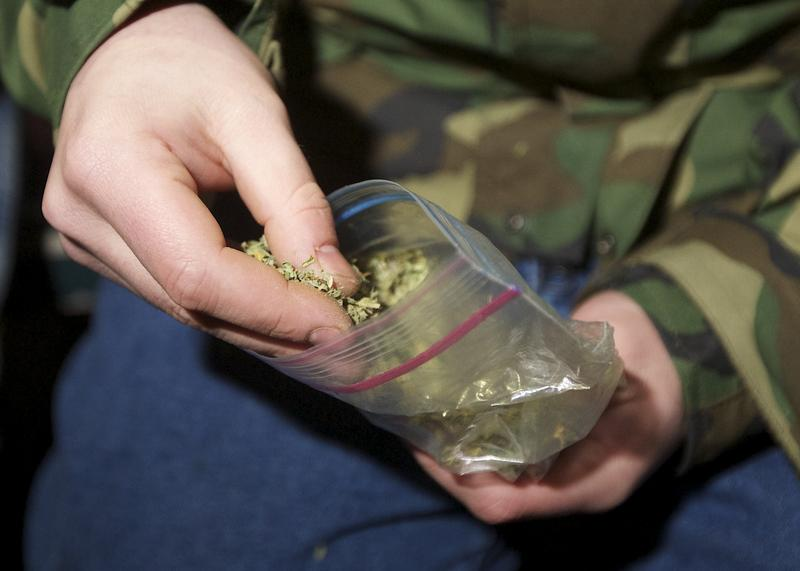 A Seattle resident takes marijuana from a plastic bag shortly after a law legalizing the recreational use of marijuana took effect on December 6, 2012 in Seattle, Washington.