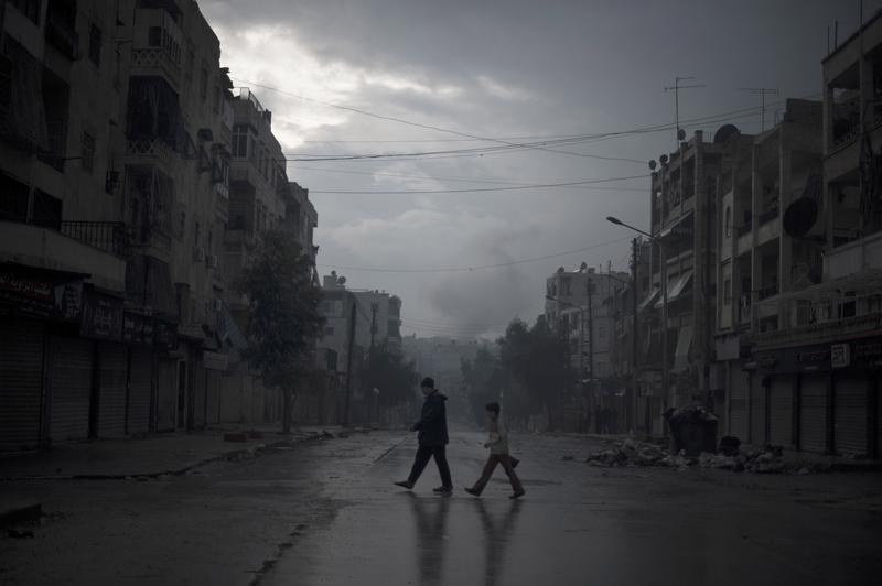A father and son return home with vegetables, as smoke from a pro-government forces artillery strike ascends in the background, in the al-Amaria neighborhood in the city of Aleppo, on January 6, 2013.