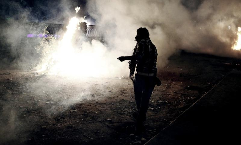 An Egyptian protester stands amongst smoke and tear gas during clashes with riot police near Tahrir Square on January 27, 2013 in Cairo, Egypt.