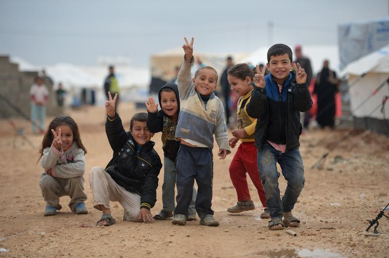 Children pose for a picture as Syrian refugees go about their daily business in the Za'atari refugee camp on February 1, 2013 in Za'atari, Jordan