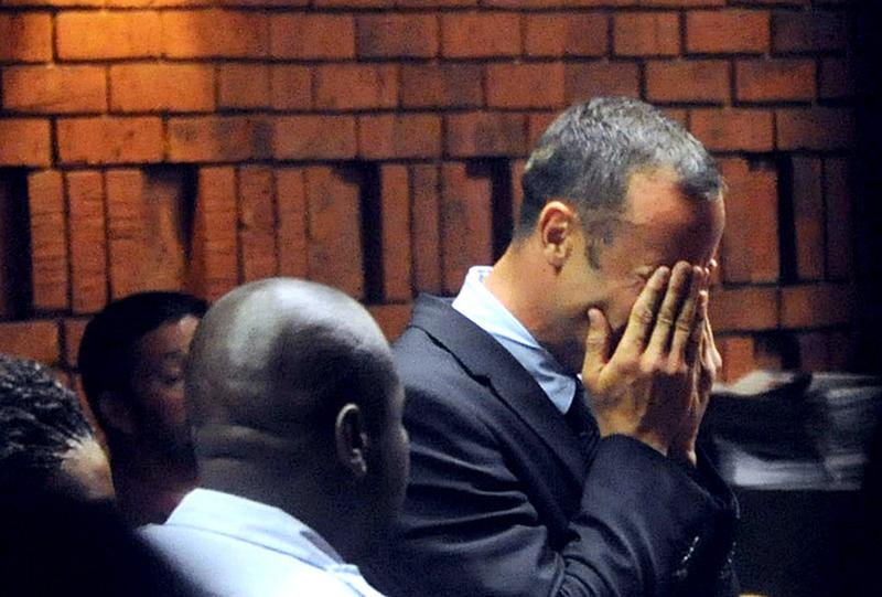 South Africa's Olympic sprinter Oscar Pistorius hides his face in his hands in the court room during his hearing on charge of murdering his model girlfriend Reeva Steenkamp.