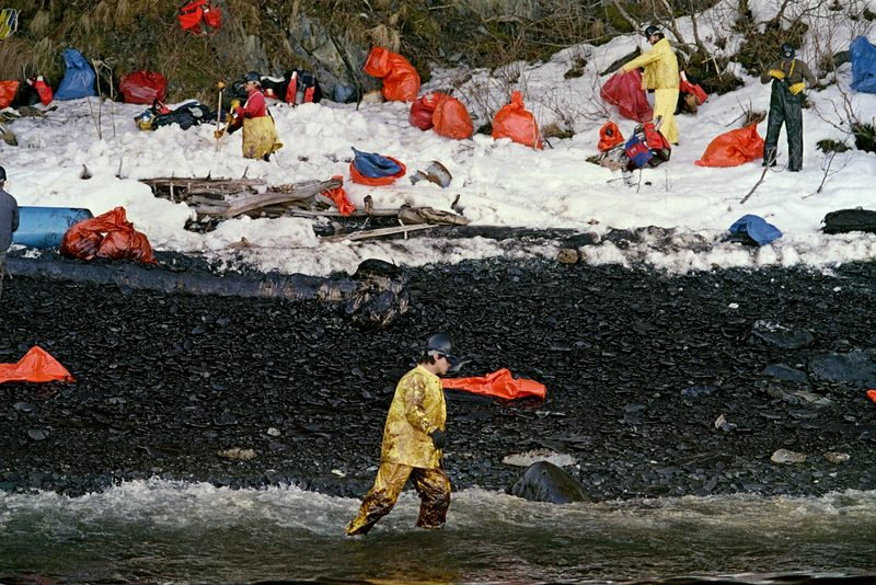 An oil cleanup worker walks through the oily surf at Naked Island on Prince Williams Sound, April 02, 1989.