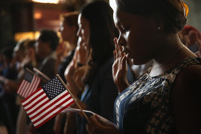 Shaun Lawrence of Jamaica takes an oath of citizenship during a naturalization ceremony at the Chicago Cultural Center on July 3, 2013 in Chicago, Illinois.