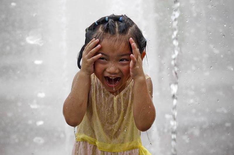 This picture taken on August 11, 2013 shows a laughing child playing in a fountain to cool off as Shanghai continues to be hit by hotter than usual weather.