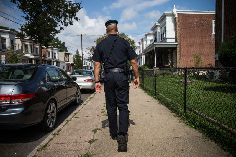 Officer Adam Fulmore, of the Camden County Police Department, goes on a foot patrol on August 22, 2013 in the Parkside neighborhood of Camden, New Jersey.