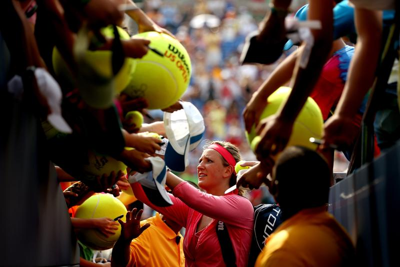 Victoria Azarenka of Belarus signs autographs for fans following her victory in the women's singles third round match against Alize Cornet of France on Day Six of the 2013 US Open.