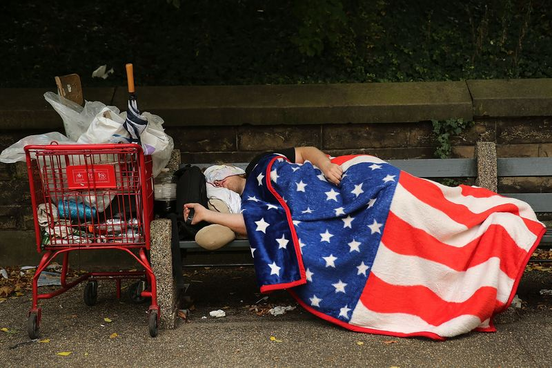 A homeless man sleeps under an American Flag blanket on a park bench on September 10, 2013 in New York City