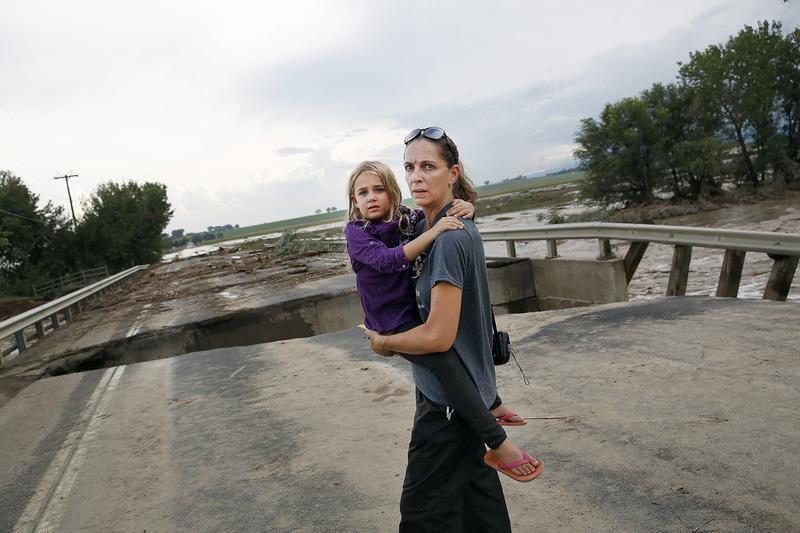 Samantha Kinzig of Longmont, Colorado and her five year-old daughter Isabel take in a closer view of a damaged bridge on Weld County Road 1 on September 13, 2013 in Longmont, Colorado.