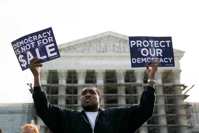 Cornell Woolridge holds signs as he rallies against money in politics before the Supreme Court hears arguments in  McCutcheon v. FEC on October 8, 2013 in Washington, DC.