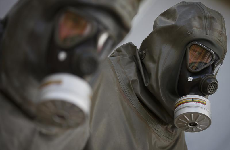 Employees in protective gear are seen during a demonstration in a chemical weapons disposal facility at GEKA.