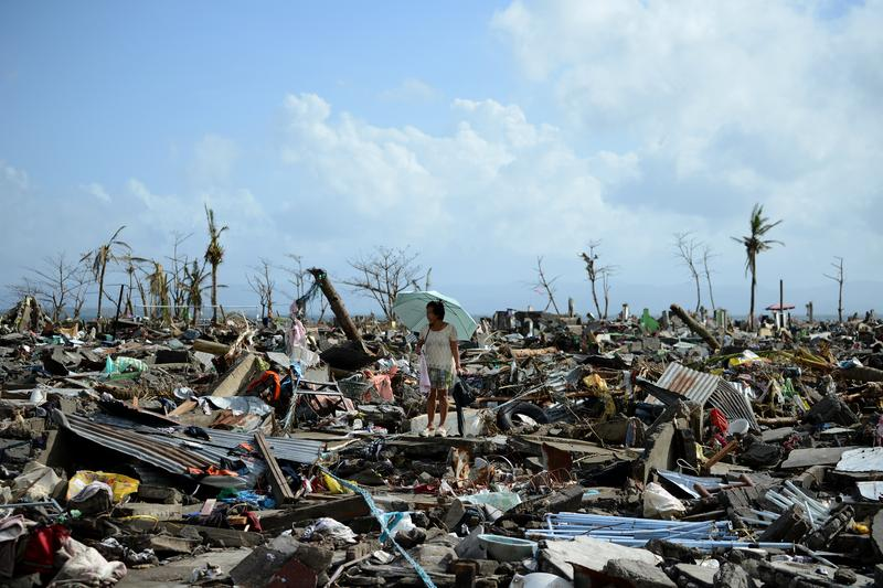A surivor walks among the debris of houses destroyed by Super Typhoon Haiyan in Tacloban in the eastern Philippine island of Leyte on November 11, 2013.