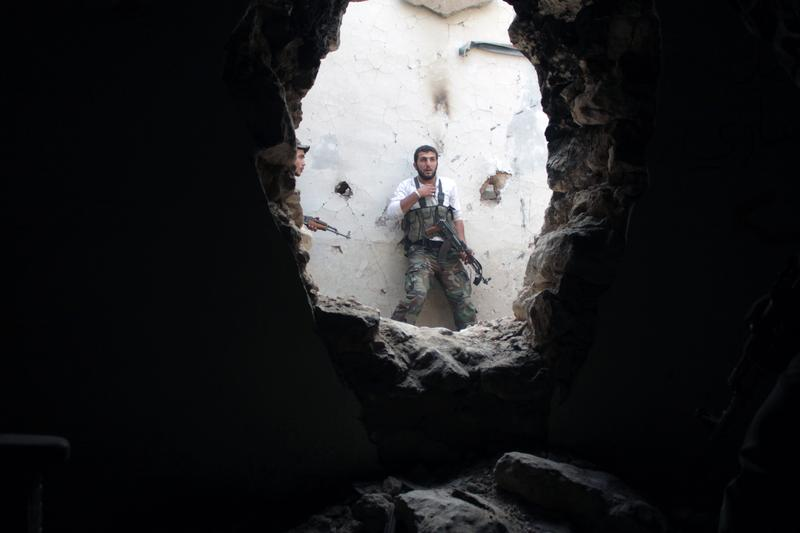 Rebel fighters hold a position in a damaged building during clashes with Syrian government forces in the northeastern city of Deir Ezzor, on November 11, 2013.