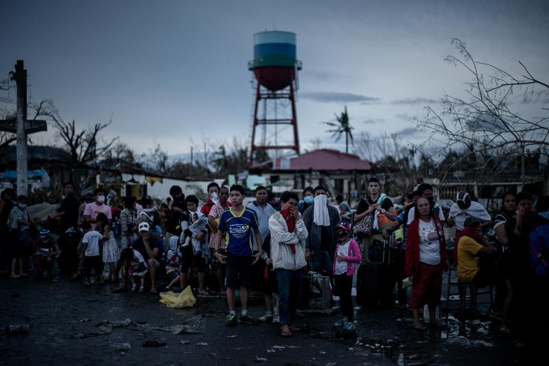 Typhoon victims wait outside the airport in Tacloban, on the eastern island of Leyte on November 12, 2013 after Super Typhoon Haiyan swept over the Philippines.