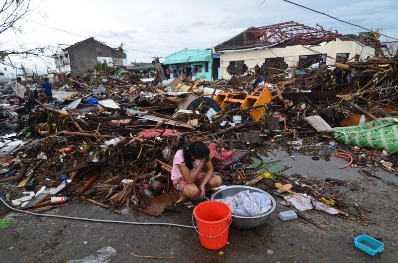A girl pauses while washing clothes amongst the debris in an area devastated by Typhoon Haiyan on November 12, 2013 in Leyte, Philippines.
