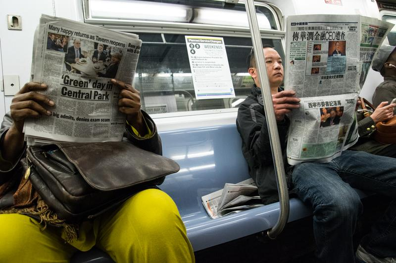 Passengers read newspapers in English and Chinese on the subway in Manhattan.