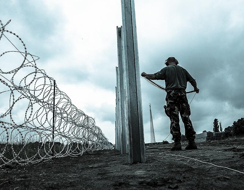 Members of the Hungarian Defence Force install barbed wire on the Hungarian-Serbian border to prevent illegal migrants from entering the country near Kelebia village in Hungary on August 17, 2015.