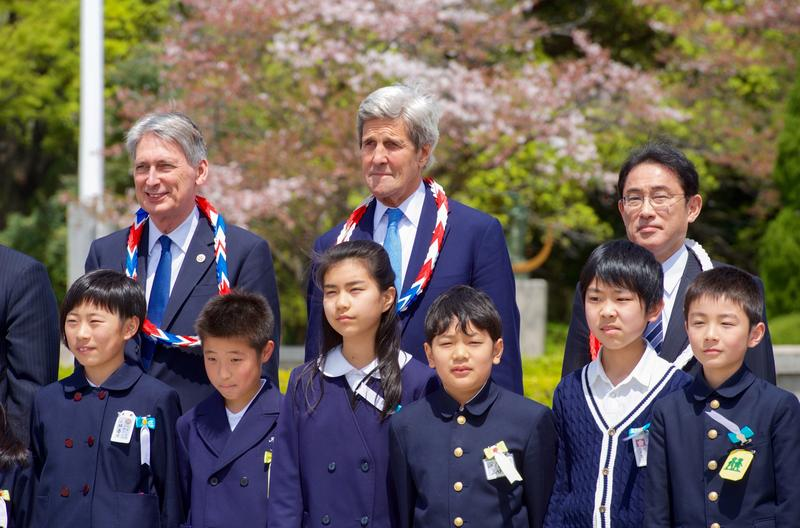 U.S. Secretary of State John Kerry and his counterparts stand with school children on April 11, 2016, after laying wreaths at the Hiroshima Peace Memorial Park.