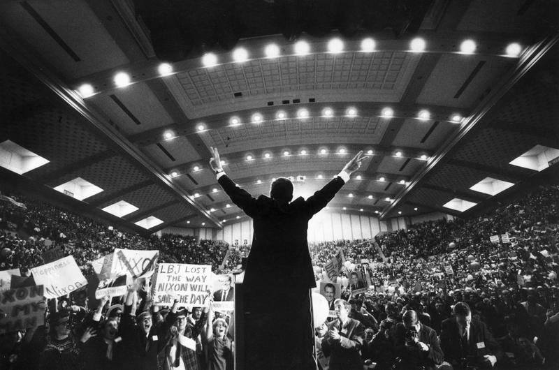 1968: Republican presidential candidate Richard Nixon standing on stage with his back to the camera in front of an arena of supporters giving the victory 'V' sign with both hands.