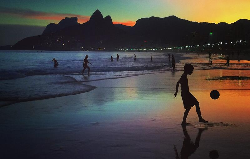 A young boy plays football at sunset on June 8, 2014 in Rio de Janeiro, Brazil.