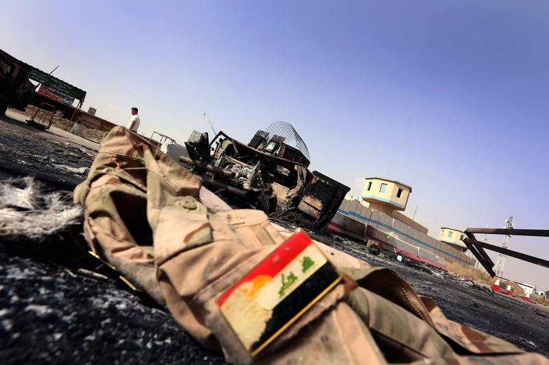 The jacket belonging to an Iraqi Army uniform lies on the ground in front of the remains of a burnt out Iraqi army vehicle some 10km of east of the northern city of Mosul, on June 11, 2014.