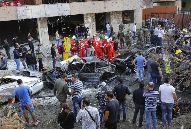 Onlookers watch as Lebanese rescue teams and security forces inspect at the scene of a powerful blast in southern Beirut which killed at least 10 people on November 19, 2013 near the Iranian embassy.