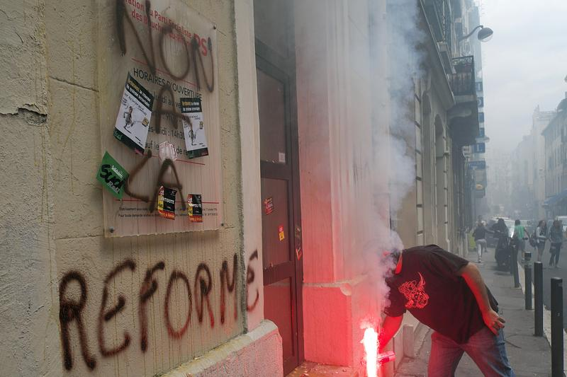A striking employee of the French SNCF railway company uses a flare to write on the asphalt as they demonstrate in front of the French Socialist Party (PS) headquarters in Marseille on June 18, 2014