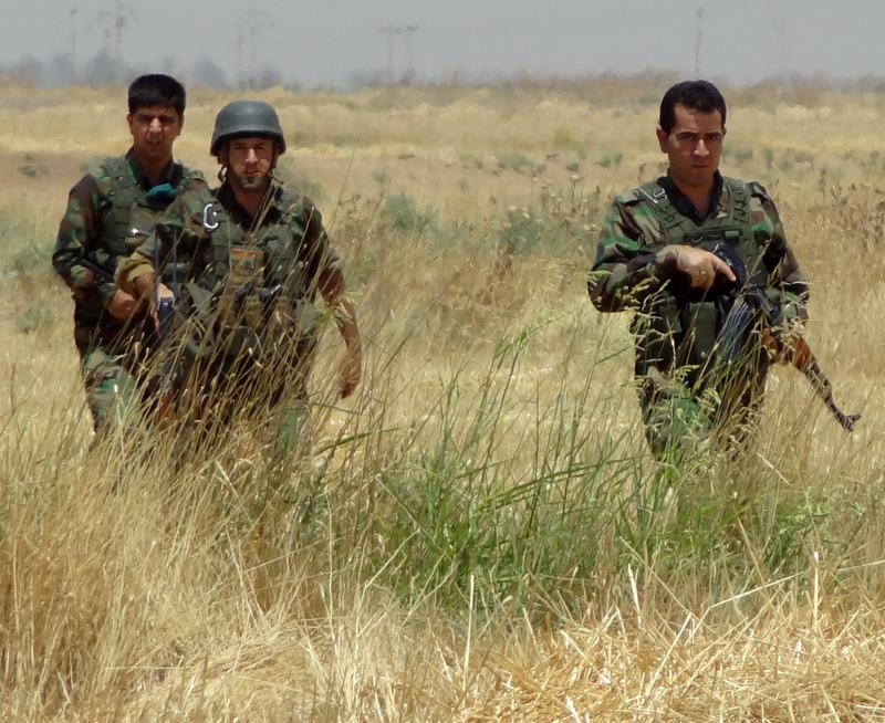 Members of Kurdish security forces patrol a field around the Jihadist-controlled Bashir region.