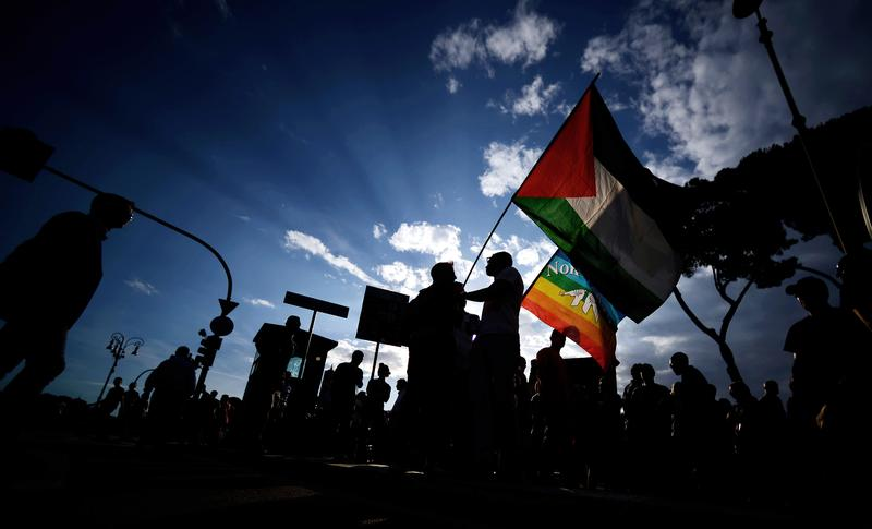 Demonstrators hold a Palestinian and peace flag during a rally against the Israeli military offensive in the Gaza strip in downtown Rome on July 11, 2014.