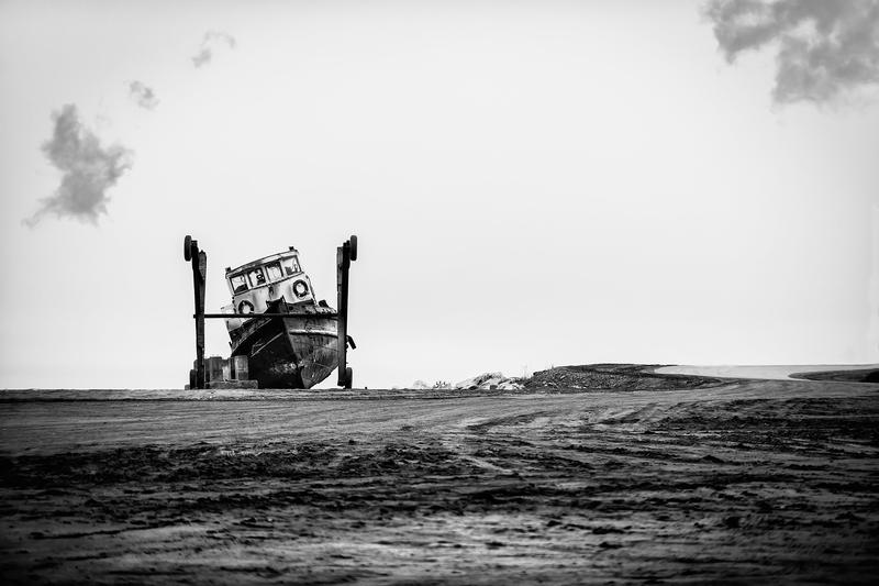 Frozen in and leaking oil, this tug boat was pulled from the small boat harbor in Nome, Alaska and now sits abandoned.