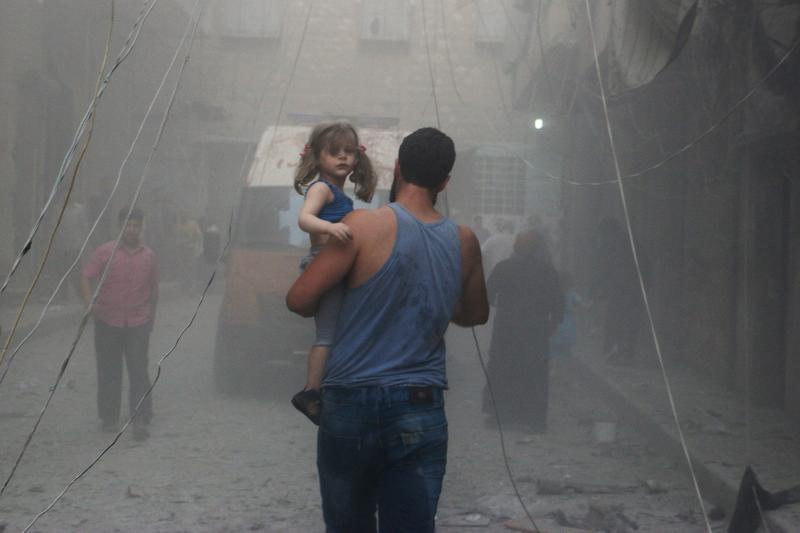 A Syrian man carries a girl on a street covered with dust following a air strike by government forces in the northern city of Aleppo on July 15, 2014.