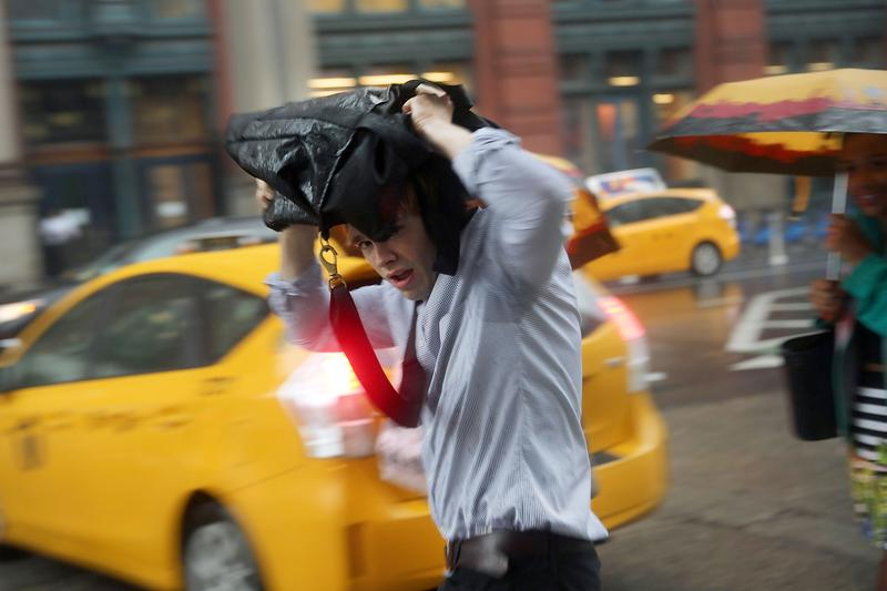 A man takes cover during an afternoon downpour and thunderstorm in Manhattan on July 15, 2014.
