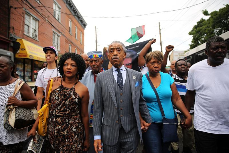 The Rev. Al Sharpton marches with family members of Eric Garner (right) and hundreds of others during a demonstration against the death of Eric Garner after he was taken into police custody.