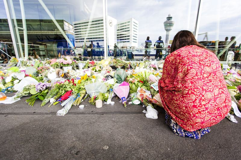 A woman kneels by flowers layed at a remembrance spot at Schiphol Airport, near Amsterdam, July 20, 2014. Malaysia Airlines flight MH17, which took off at Schiphol airport, was blown out of the sky.