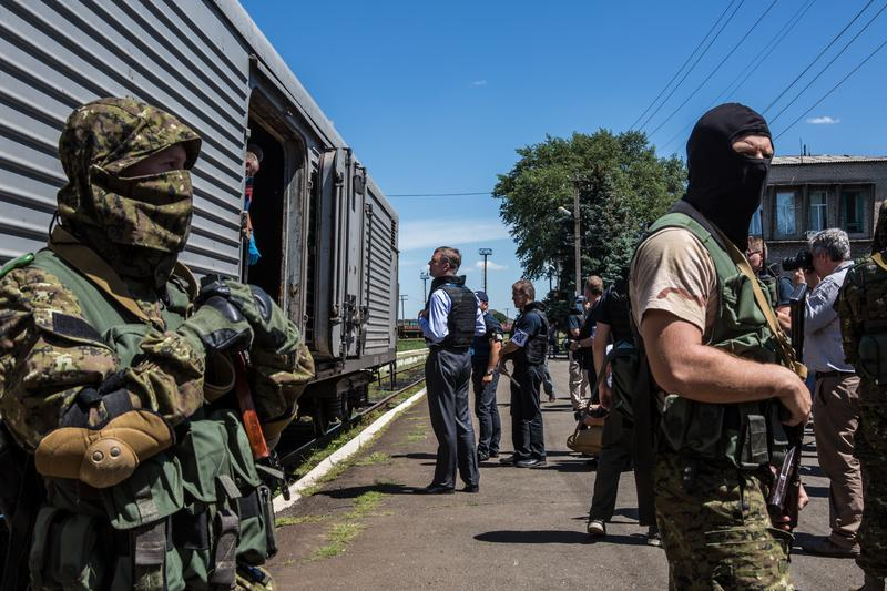 Surrounded by separatists, Alexander Hug (C), Deputy Chief Monitor of OSCE Special Monitoring Mission to Ukraine, visits a train containing the bodies of victims of the flight MH17. July 21, 2014