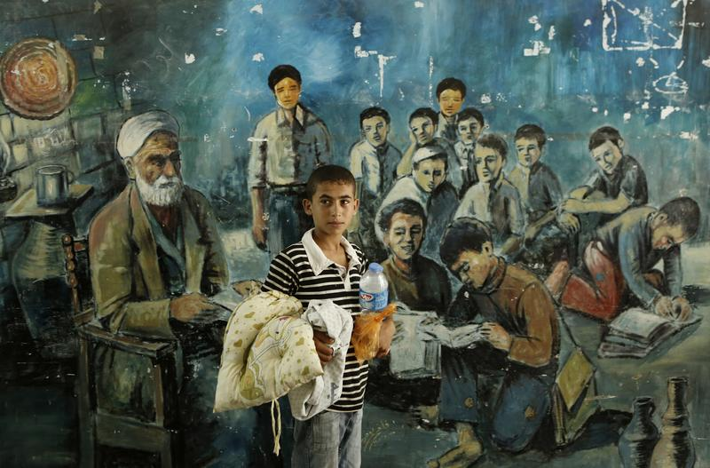 A displaced Palestinian boy from Beit Hanun in the northern Gaza Strip stands on July 23, 2014 in front of a mural painting at a UN school in the refugee camp of Jabalia.