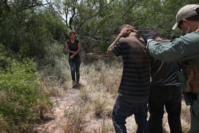 U.S. Border Patrol agents detain undocumented immigrants in Texas. Tens of thousands of unaccompanied minors have crossed illegally into the United States this year.